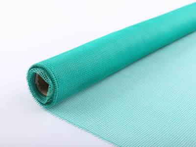 This is a roll of fiberglass window screen in green.