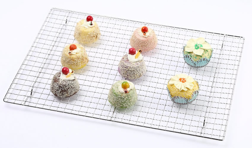 There is a stainless steel crimped wire mesh baking rack with several cakes on it.