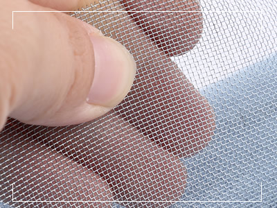 A hand is holding a piece of bluish galvanized window screen.