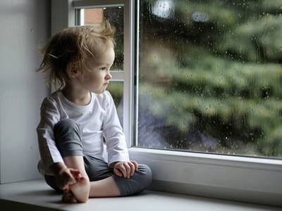 A baby girl sitting on the sill.