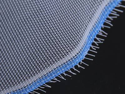 A piece of plain weave plastic screen with blue edge on the black background.