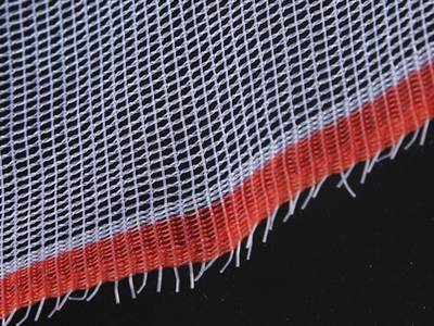 A piece of warp knitting plastic screen with red edge on the black background.