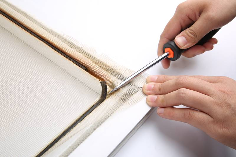 A worker is remove the old splines from frame with a screwdriver.