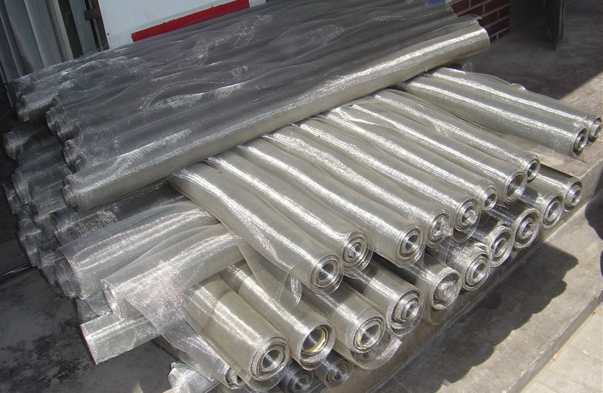 Many coils of stainless steel window screens placed orderly on the ground.