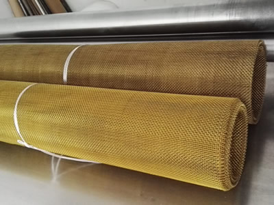 Two rolls of brass window screen on the table.